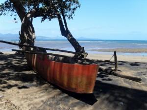 Musicale plage à marée basse avec en premier plan une pirogue à balancier traditionnelle (laka)
