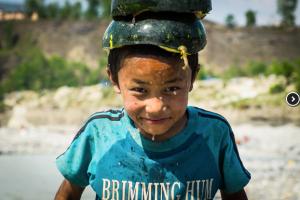 Un enfant népalais au bord de la rivière en train de jouer avec une pastèque!